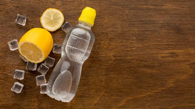 Bouteille en plastique d'eau et espace copie de citron