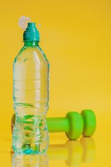 Bouteille en plastique d'eau minérale sur fond jaune vif