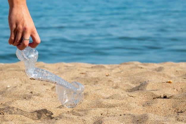 La bouteille en plastique est sur la plage laissée par le touriste