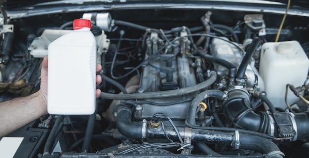 Bouteille en plastique d'huile de machine avec un moteur de voiture.