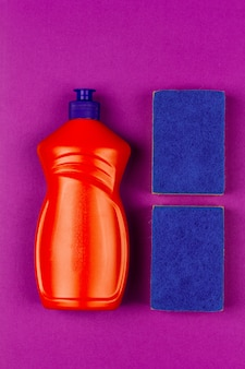 Bouteille en plastique orange contenant du liquide vaisselle et une éponge bleue