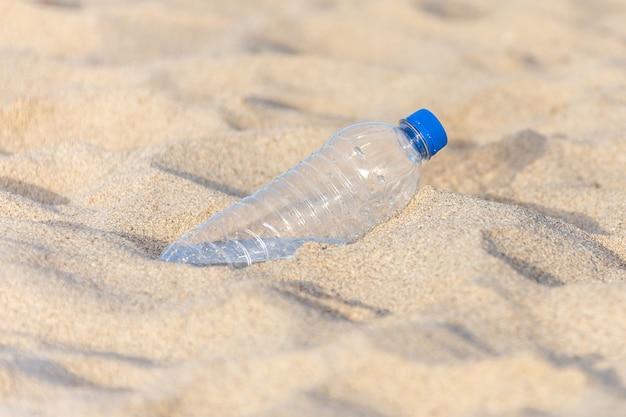 Bouteille en plastique sur la plage laissée par le touriste