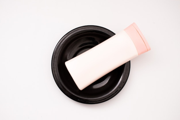 Bouteille en plastique sur une plaque isolée sur fond blanc