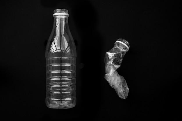 Une bouteille en plastique pressée et entière sur un mur noir. le concept de sauvegarde de l'environnement.