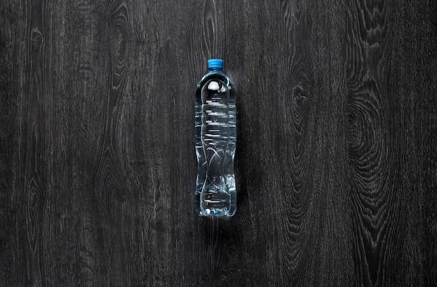 Bouteille en plastique simple avec de l'eau pure contre la surface en bois