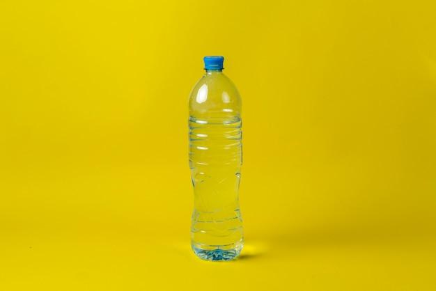 Bouteille en plastique simple avec de l'eau pure contre la surface colorée