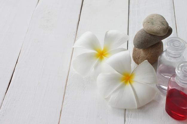 La bouteille de plumeria et gel est placée sur un plancher en bois blanc.