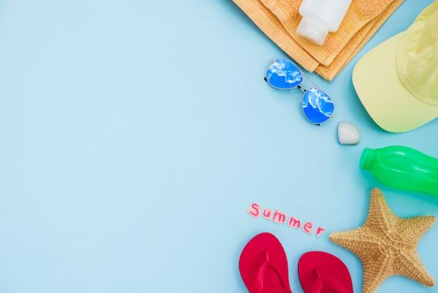 Bouteille près d'une serviette avec étoile de mer et capuchon avec lunettes de soleil et tongs