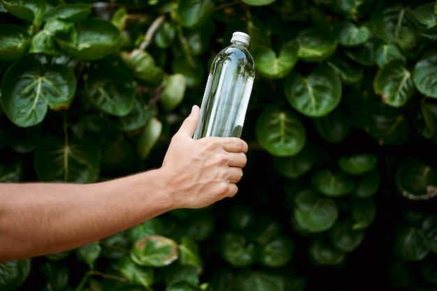 Bouteille réutilisable en verre transparent de l'eau tenue dans la main