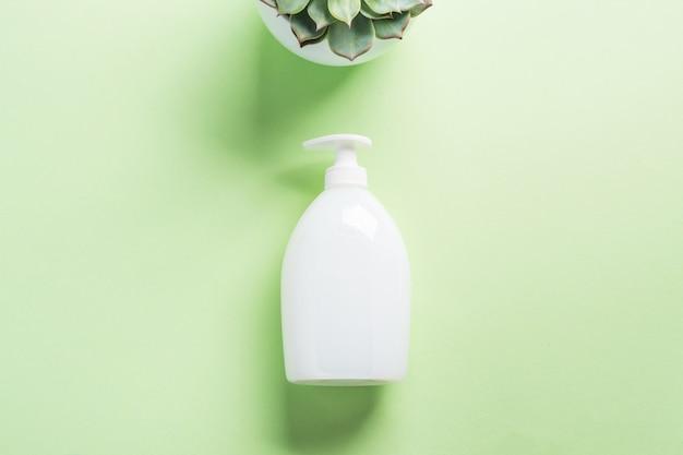 Bouteille de savon blanc naturel sur vert pastel
