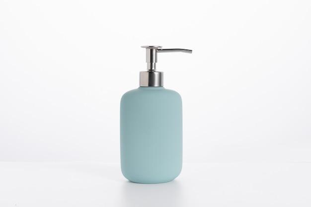 Bouteille de savon en verre bleu isolé sur un mur blanc