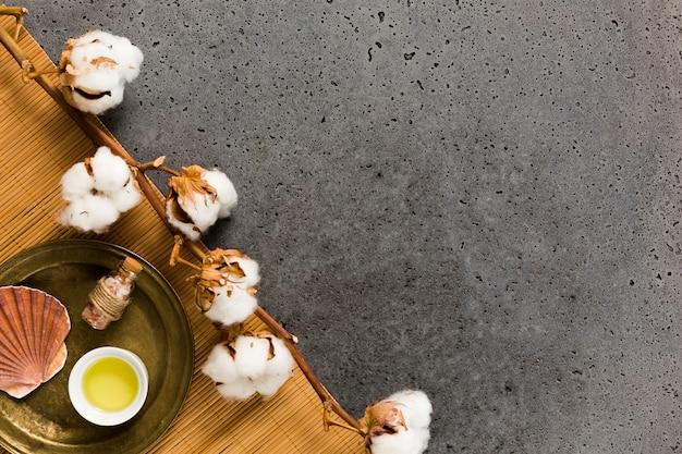 Bouteille de sel avec coquille de mer et huile près de pantalon de coton