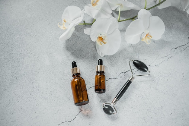 Bouteille de sérum ou d'huile essentielle avec rouleau de massage guasha pour spa et soins naturels de la peau, soins naturels du corps et de la peau, maquette de marque de produit cosmétique spa