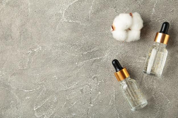 Bouteille de sérum ou d'huile avec pipette et brindille de coton sur une surface grise avec espace de copie