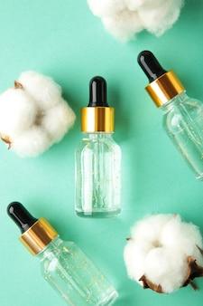 Bouteille de sérum ou d'huile avec pipette et brindille de coton sur la surface de la menthe