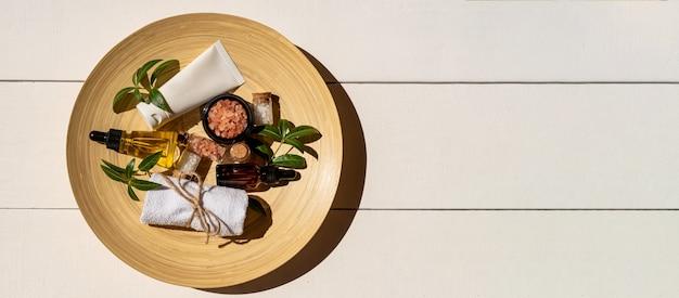 Bouteille de sérum hydratant, crème pour le visage, sel rose de l'himalaya et serviette sur plaque de bambou. concept de soins de la peau du visage bio. copiez l'espace pour le texte.
