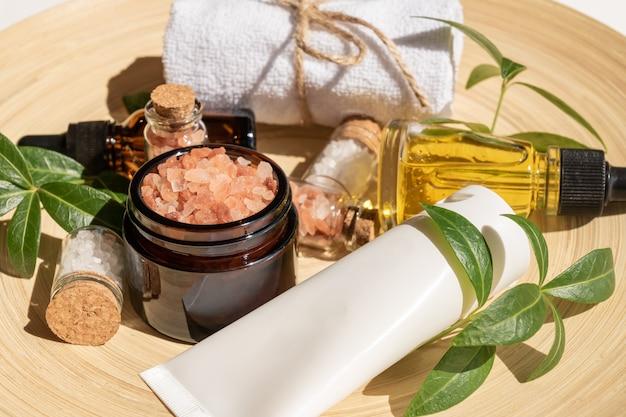 Bouteille de sérum hydratant, crème pour le visage, sel rose de l'himalaya et serviette sur plaque de bambou. concept de soins de la peau du visage bio.