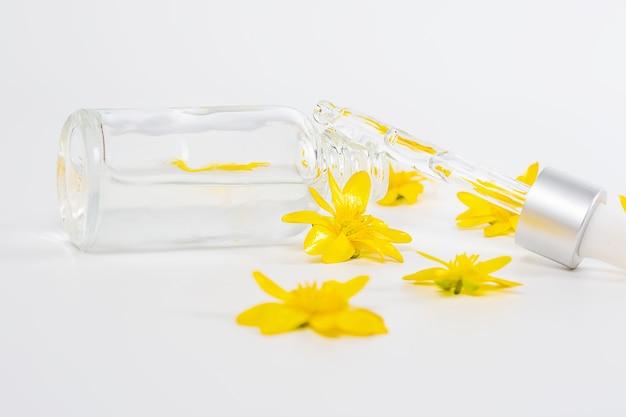Une bouteille avec un sérum de pipette sur un fond blanc entouré de fleurs printanières jaunes