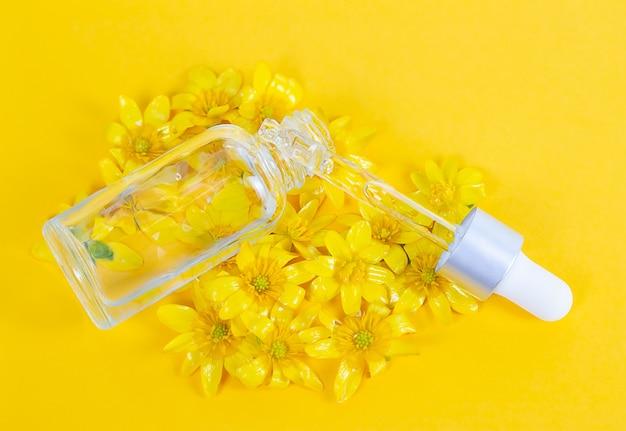 Une bouteille avec un sérum de pipette sur un fond jaune entouré de fleurs printanières
