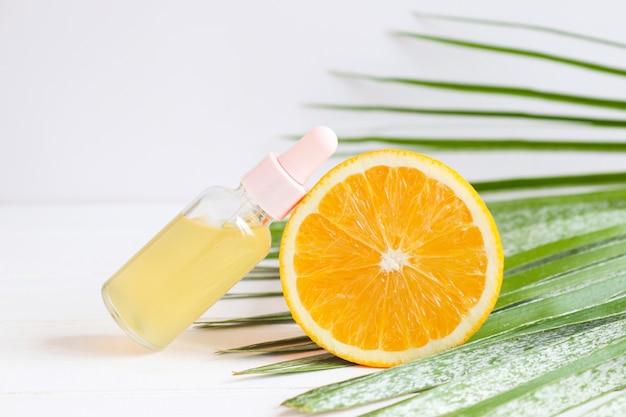 Bouteille de sérum de soin cosmétique avec compte-gouttes orange et feuille de palmier concept beauté et spa