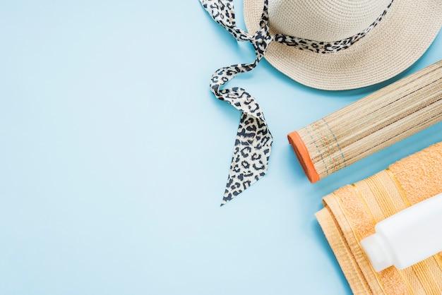 Bouteille sur une serviette près du tapis et du chapeau