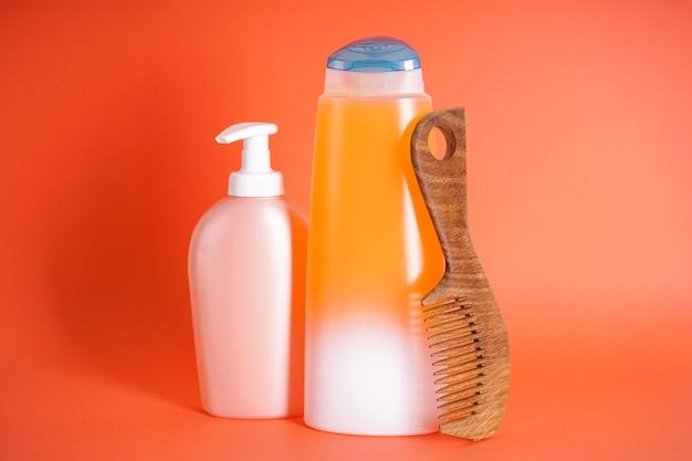 Bouteille de shampoing, distributeur de savon, brosse à cheveux en bois sur fond orange.