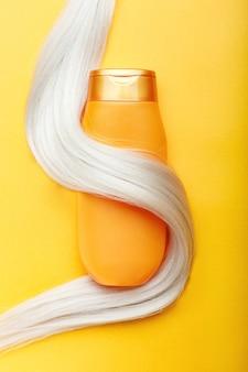 Bouteille de shampoing enveloppée dans une mèche de cheveux blonds sur fond de couleur orange
