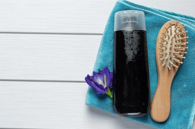 Bouteille de shampoing de fleur de pois papillon mis sur fond de bois blanc