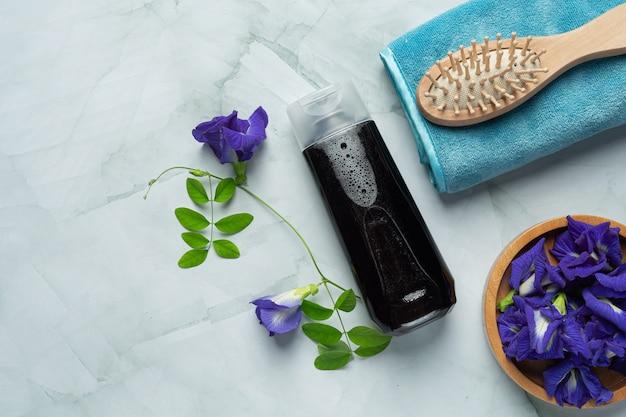 Bouteille de shampoing de fleur de pois papillon mis sur fond de marbre blanc