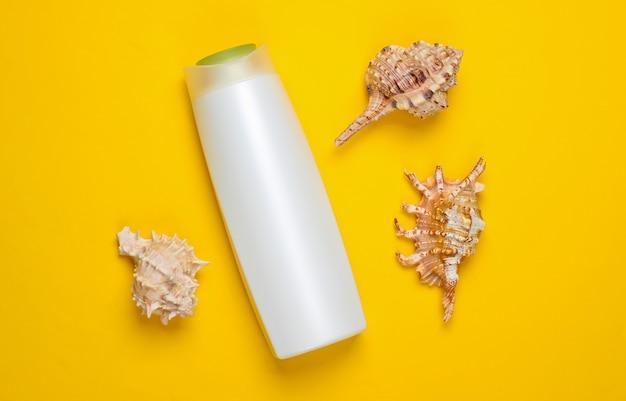 Bouteille de shampooing avec coquilles sur un jaune