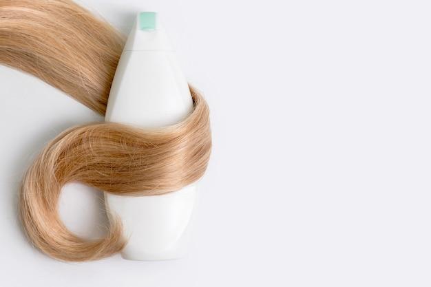 Bouteille de shampooing ou de revitalisant enveloppée dans une mèche de cheveux blonds bouclés isolés sur fond clair, vue de dessus. mise à plat, copiez l'espace pour le texte. cosmétiques de soins capillaires, produits de soins capillaires de beauté, traitement des cheveux.