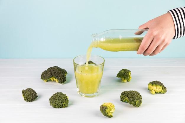 Bouteille de smoothie de brocoli frais versé dans un verre