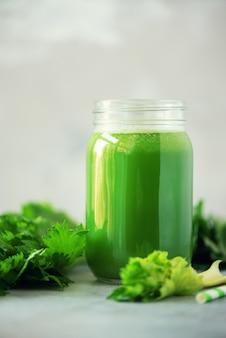 Bouteille de smoothie de céleri vert sur fond de béton gris
