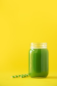 Bouteille de smoothie de céleri vert sur fond jaune