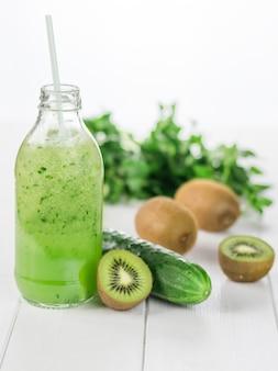 Bouteille de smoothie concombre, kiwi et concombre frais sur une table en bois blanc.