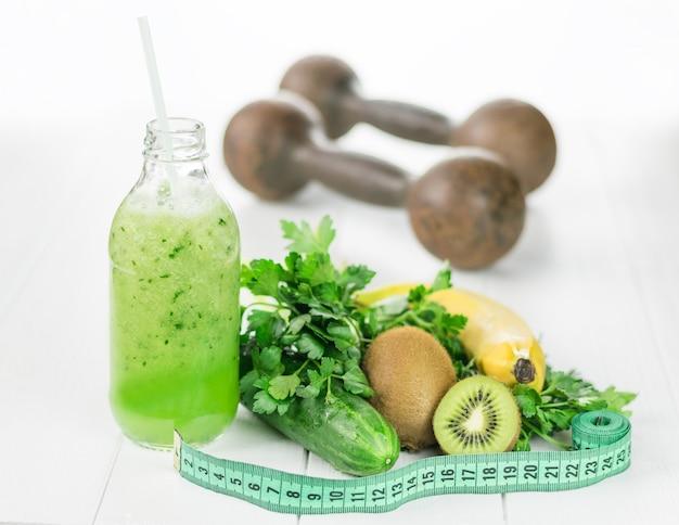Une bouteille de smoothies au concombre, des fruits et du ruban à mesurer sur une table blanche.