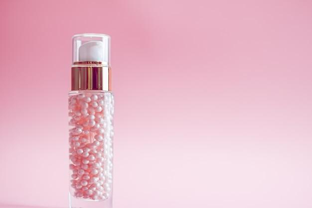 Bouteille de soins de la peau sur fond rose produits de beauté et cosmétiques de luxe