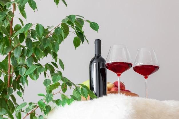 Bouteille sombre et deux verres de vin rouge sur table dans une cuisine moderne
