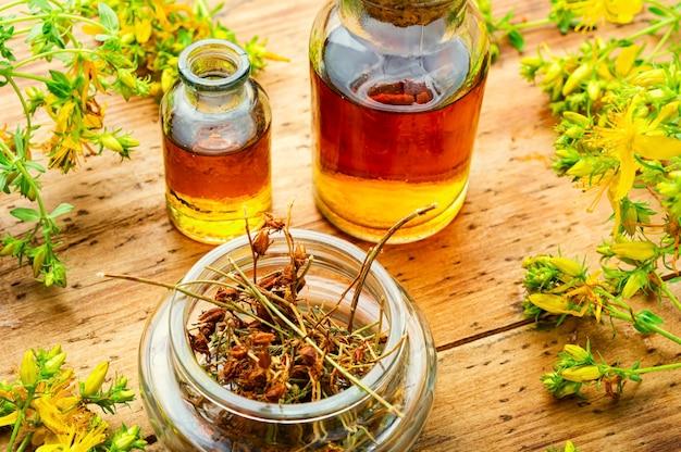 Bouteille de teinture de guérison ou d'élixirs à base de plantes. extrait de fleur d'hypericum. herbes médicinales
