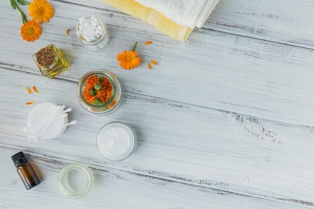 Une bouteille de teinture de souci ou d'infusion, de crème ou de baume avec des fleurs de calendula fraîches et sèches et un coton et des bâtons sur bois blanc