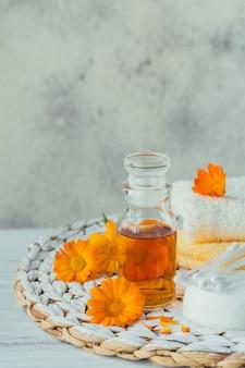 Une bouteille de teinture de souci ou d'infusion avec des fleurs de calendula fraîches et un coton et des bâtons sur un fond blanc. médecine alternative à base de plantes naturelles, herbes médicinales et curatives.