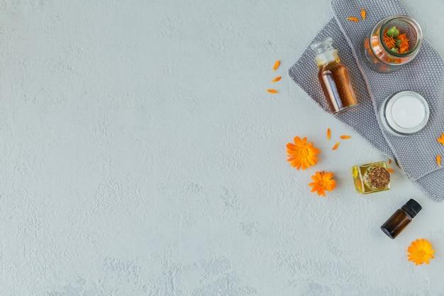 Une bouteille de teinture de souci ou d'infusion, de pommade, de crème ou de baume avec des fleurs de calendula fraîches et sèches sur bois blanc