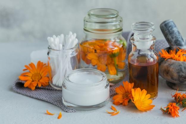 Une bouteille de teinture de souci ou d'infusion, de pommade, de crème ou de baume avec des fleurs de calendula fraîches et sèches et un coton et des bâtons sur blanc.
