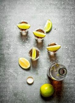Bouteille de tequila avec de la chaux et du sel sur table en pierre.