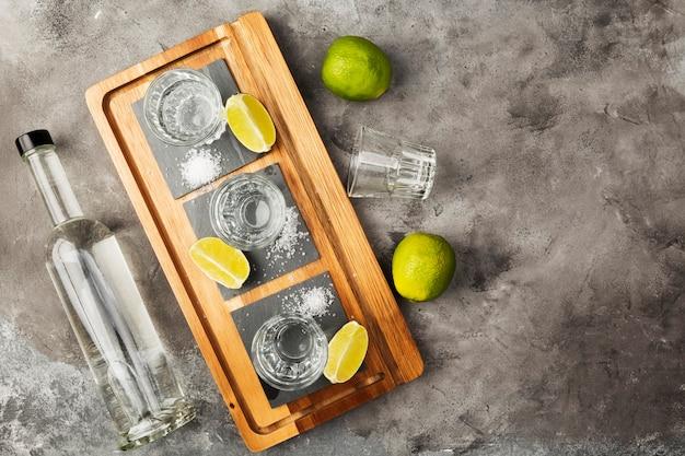 Bouteille de tequila et coups de feu, limes, sel sur planche de bois. vue de dessus, espace copie