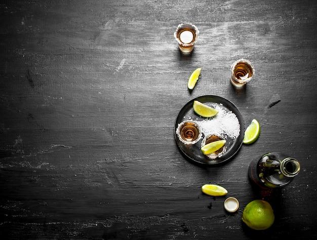 Bouteille de tequila avec verres à liqueur, citron vert frais et sel. au tableau.