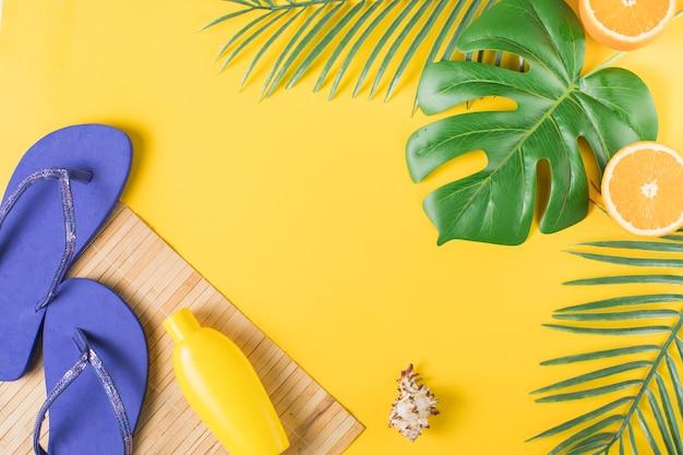 Bouteille avec des tongs sur tapis de paille et feuilles de la plante