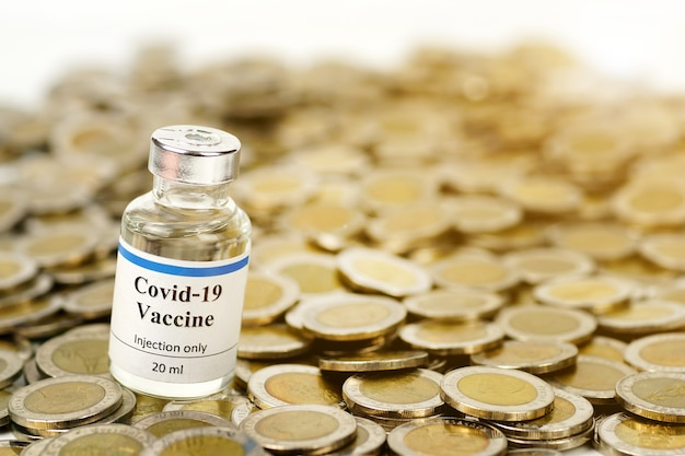 Bouteille de vaccin contre le coronavirus sur une pile de pièces