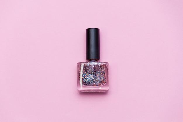 Bouteille de vernis à ongles avec paillettes et paillettes sur surface rose