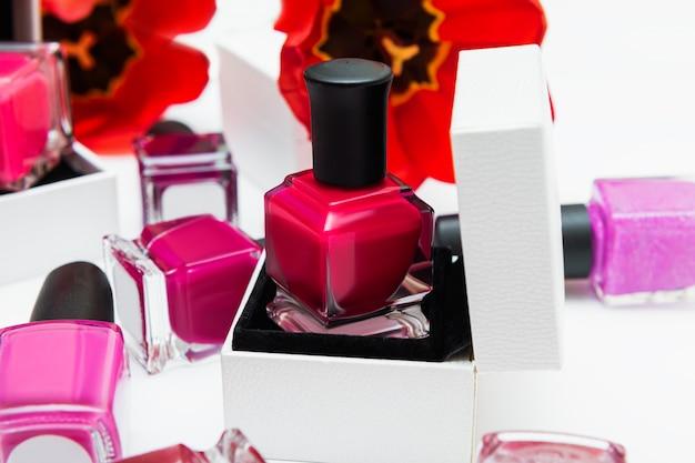 Bouteille de vernis à ongles rose et fleurs de tulipe sur fond blanc